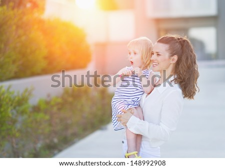 Happy mother and baby in front of house building looking on copy space - stock photo