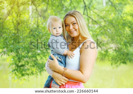 Happy mother and baby in sunny summer day - stock photo