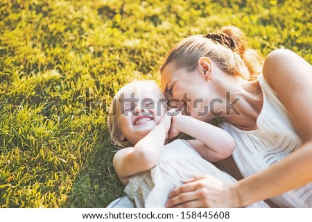 Happy mother and baby laying on meadow - stock photo