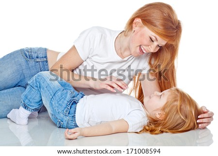 Happy mother and baby lying in studio on a white background
