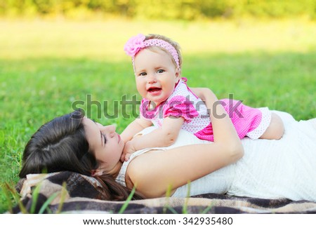 Happy mother and baby lying together on grass in summer day - stock photo