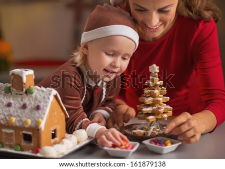 Happy mother and baby making christmas cookie house in kitchen - stock photo