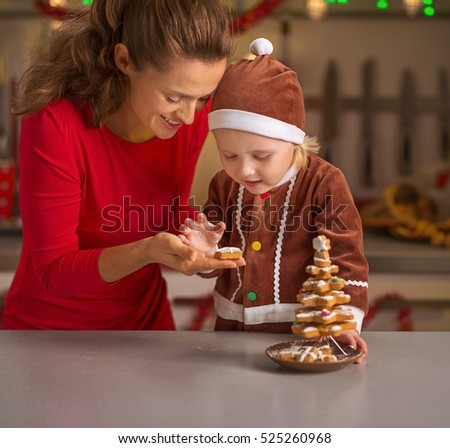 Happy mother and baby making christmas tree from cookies