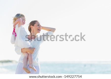 Happy mother and baby on beach looking into distance - stock photo