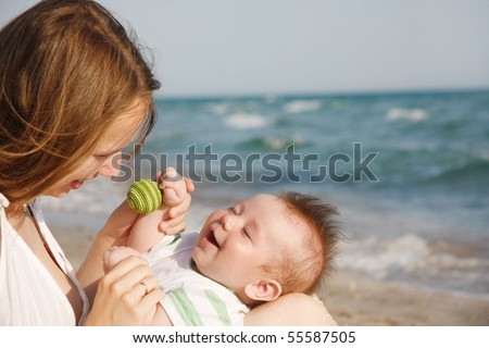 happy mother and baby on sea background - stock photo