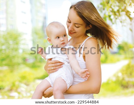 Happy mother and baby outdoors walking in summer day - stock photo