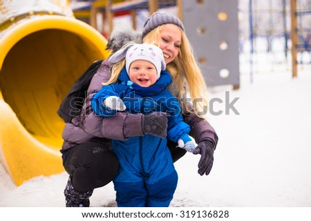 Happy mother and baby playing evergreen spruce in winter park  - stock photo