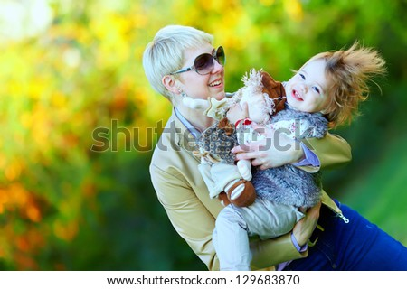 happy mother and baby playing in colorful park - stock photo