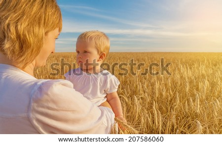 Happy mother and baby playing on a wheat field - stock photo