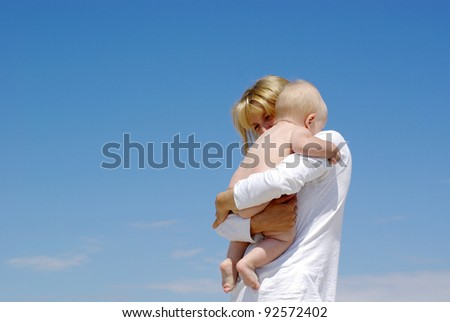 happy mother and baby playing on sky background - stock photo
