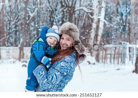 Happy mother and baby playing on snow in winter park