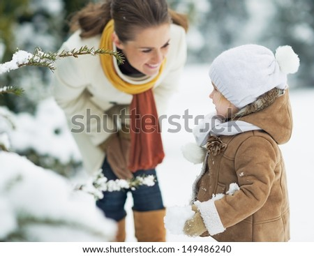 Happy mother and baby playing outdoors in winter - stock photo