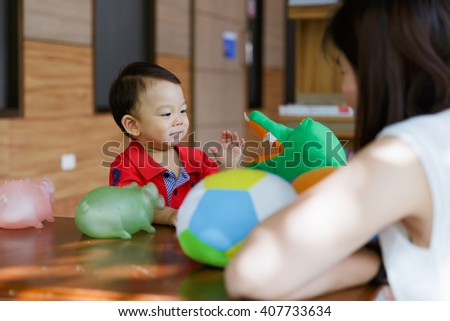 Happy mother and baby plays with toys at home