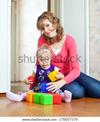Happy mother and baby plays with toys at home interior