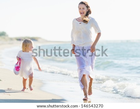 Happy mother and baby running on sea shore - stock photo