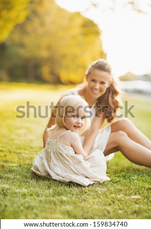 Happy mother and baby sitting on meadow in park - stock photo