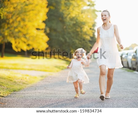 Happy mother and baby walking in city - stock photo