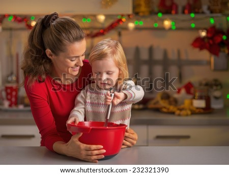 Happy mother and baby whisking dough in christmas decorated kitchen - stock photo
