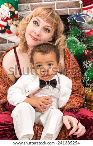 Happy mother and black baby boy cuddling by fireplace. Christmas and New Year - stock photo