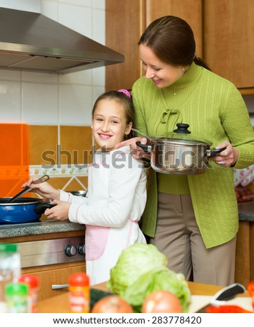 Happy mother and cheerful little daughter preparing soup together at home kitchen and smiling