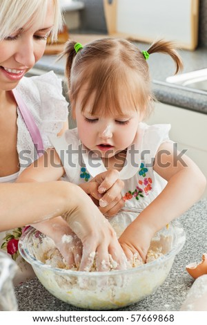 Happy mother and child baking cookies in the kitchen - stock photo