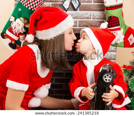 Happy mother and child boy cuddling  dressed costume Santa Claus by fireplace. Christmas and New Year. - stock photo