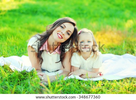 Happy mother and child daughter lying together on grass in summer day - stock photo