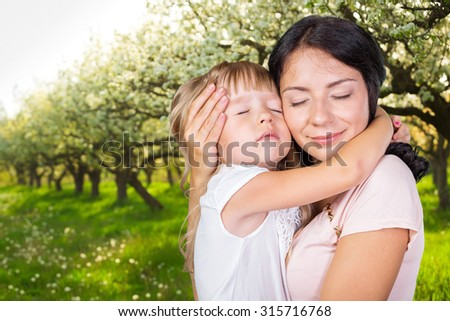 Happy mother and child girl in spring garden