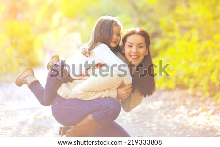 Happy mother and child having fun in autumn park - stock photo