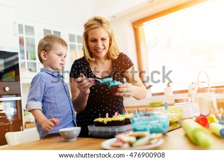 Happy mother and child in kitchen preparing cookies