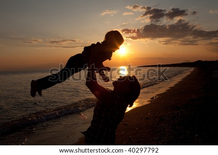 Happy mother and child in the sunset - stock photo
