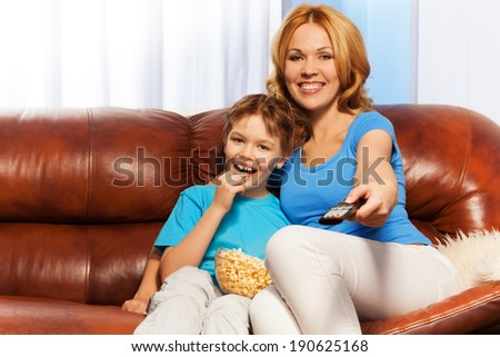 Happy mother and child sitting watching TV - stock photo
