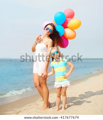 Happy mother and child with colorful balloons walking together on beach near sea - stock photo