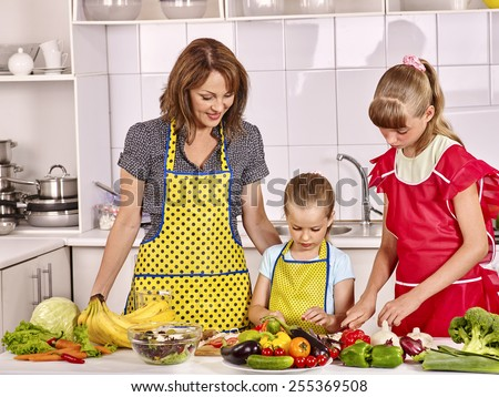 Happy mother and children cooking at kitchen. On vegetables and fruit table
