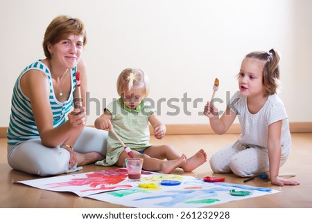 Happy mother and children painting with paint  on floor - stock photo