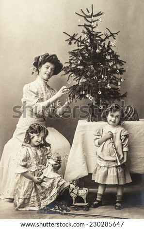 happy mother and children with christmas tree and antique toys. vintage sepia picture with original film grain and scratches