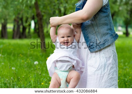 happy mother and cute baby girl playing outdoor