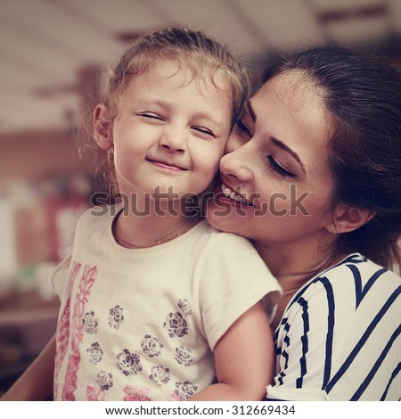 Happy mother and cute enjoying girl cuddling with love and closed eyes indoor background. Closeup vintage portrait - stock photo