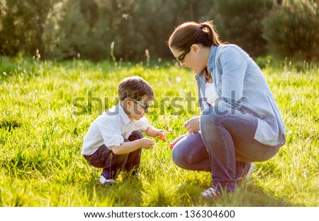 Happy mother and cute son picking a bouquet of flowers in a sunny field