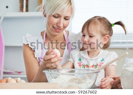 Happy mother and daughter baking together in the kitchen - stock photo