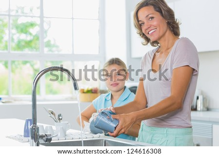 Happy mother and daughter doing the washing up together in kitchen - stock photo
