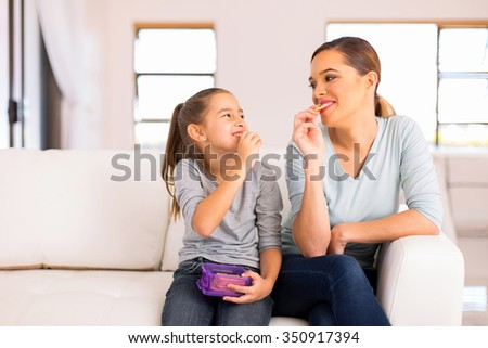 happy mother and daughter eating crackers at home - stock photo