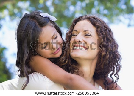 Happy mother and daughter embracing in the garden - stock photo