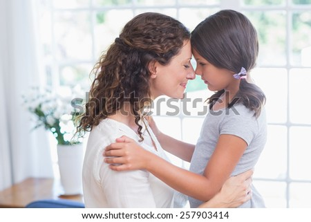 Happy mother and daughter embracing in the living room - stock photo