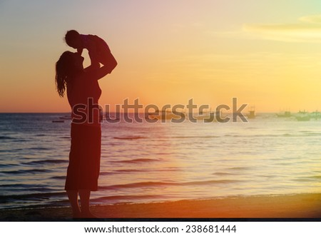 happy mother and daughter having fun at sunset beach - stock photo
