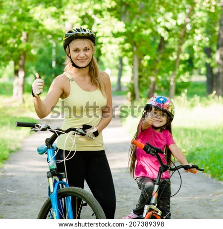 happy mother and daughter having fun, riding a bicycle and showing thumbs up - stock photo