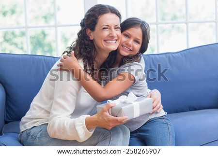 Happy mother and daughter hugging and smiling at camera in the living room