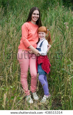 Happy mother and daughter hugging on the background of tall grass