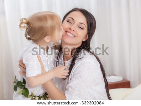 Happy Mother and daughter in bed - stock photo