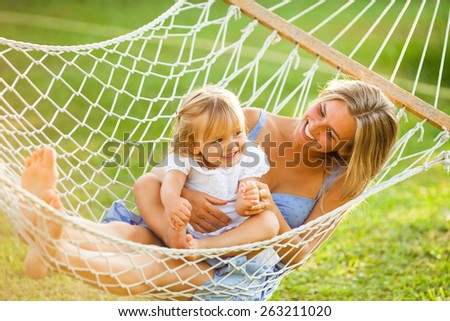 Happy mother and daughter in hammock - stock photo